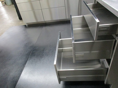 A closer view of neatly designed stainless steel cabinet with drawers.